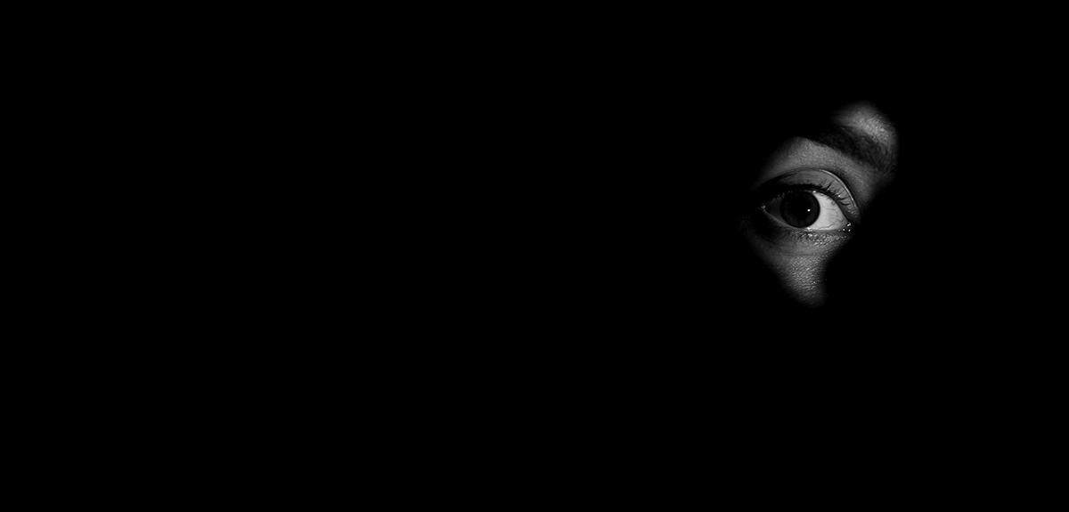 Persons eye looking through keyhole, darkness, intrusions into privacy, secret